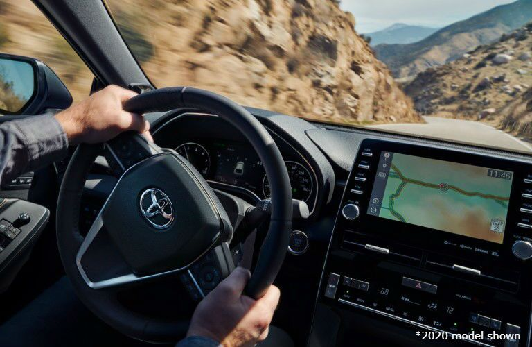 """Male hands turn the wheel of a 2021 Toyota Avalon. Text reads, """"2020 model shown."""""""