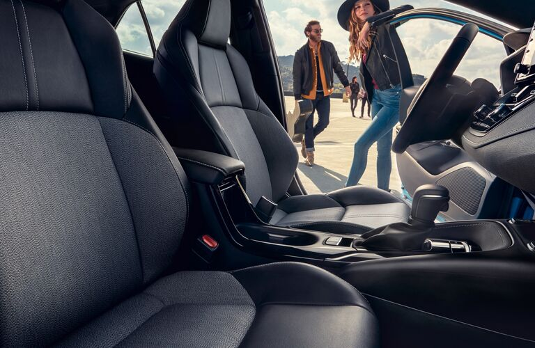 Woman in a cowboy hat leans on the open door of a 2021 Toyota Corolla Hatchback