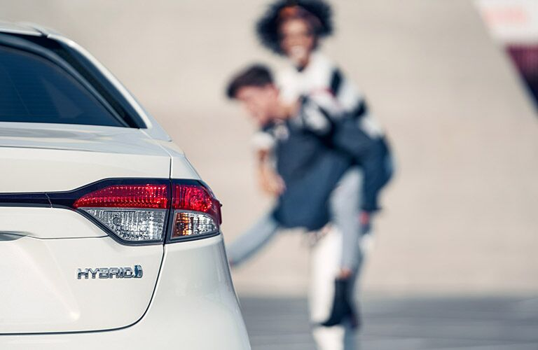 Close-up on Hybrid badge on rear of 2021 Toyota Corolla Hybrid while a man gives a woman a piggyback ride in the distance