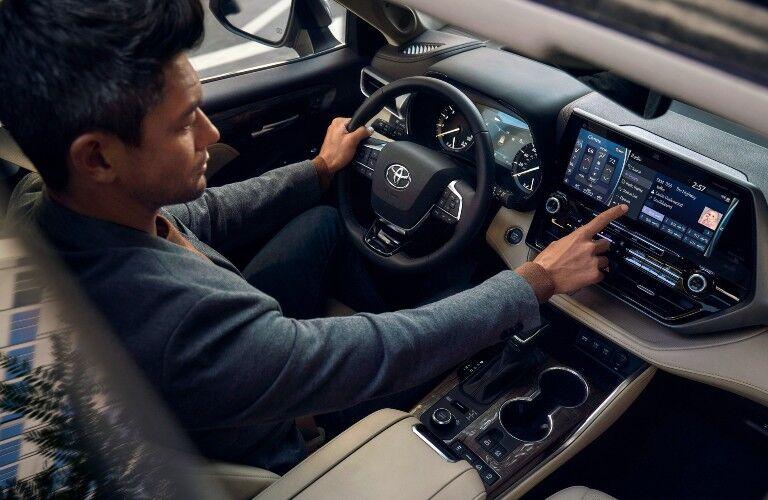 Man extends finger towards infotainment screen inside 2021 Toyota Highlander Hybrid