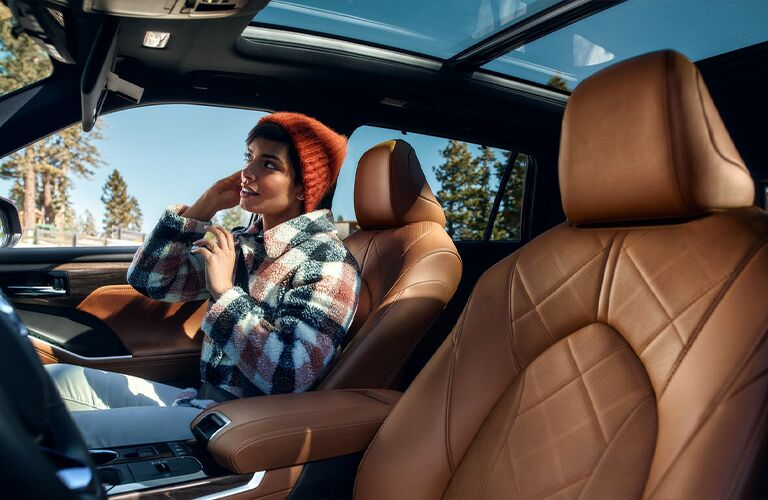 Woman enjoys herself in the passenger seat of a 2021 Toyota Highlander Hybrid