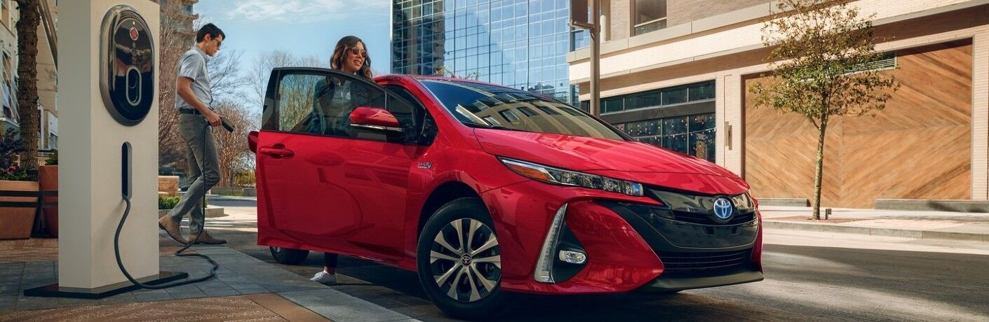 Man and woman charge a 2021 Toyota Prius Prime