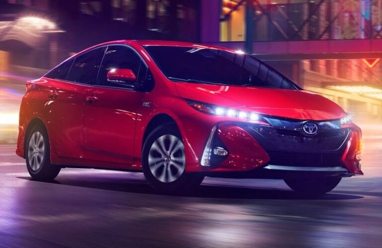 2021 Toyota Prius Prime driving down neon-lit street