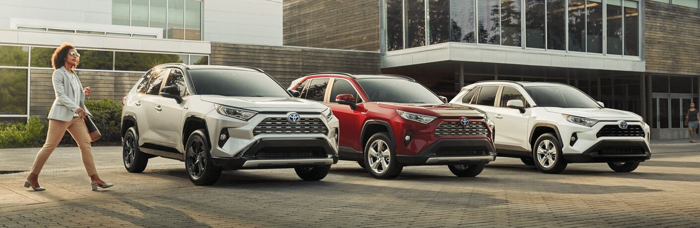 Woman struts out confidently in front of various 2021 Toyota RAV4 models