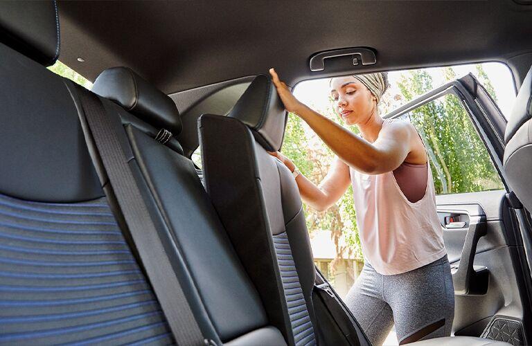 Woman adjusts seat in rear of 2021 Toyota RAV4 Hybrid