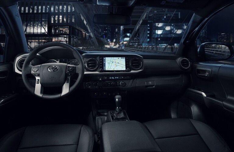 Interior front cockpit of a 2021 Toyota Tacoma in a city at night