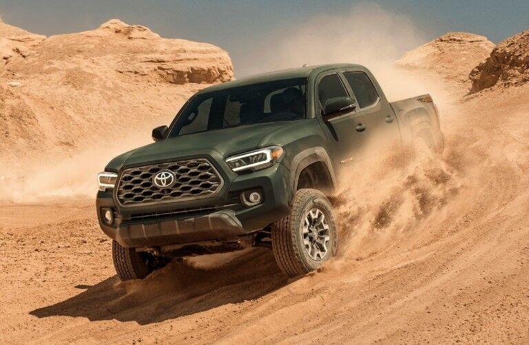 Green 2021 Toyota Tacoma kicks up sand in a desert