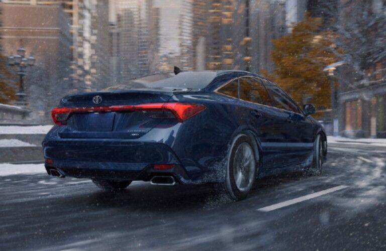Blue 2021 Avalon drives through a snowy street