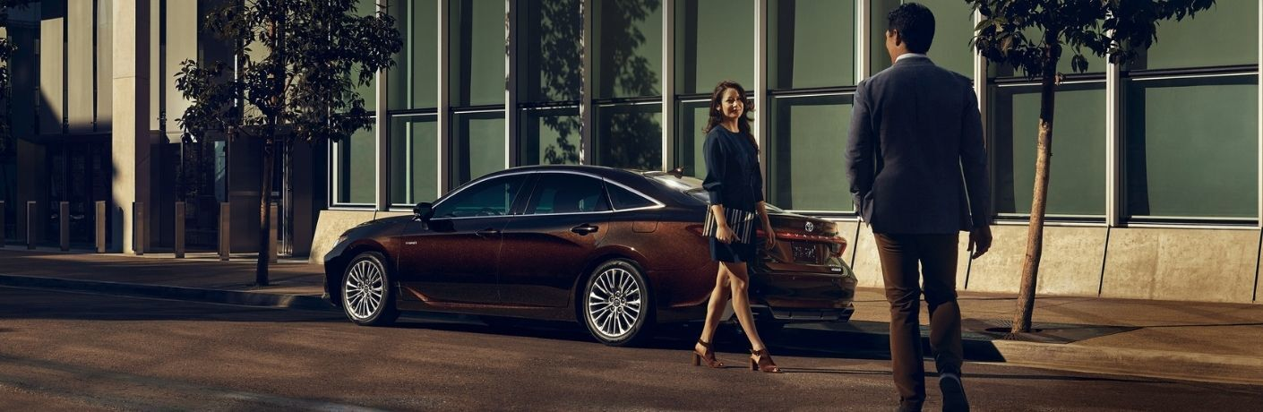 Man and woman greet one another outside a 2021 Toyota Avalon Hybrid