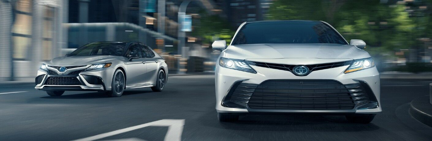 Two 2021 Toyota Camry models ride on a road