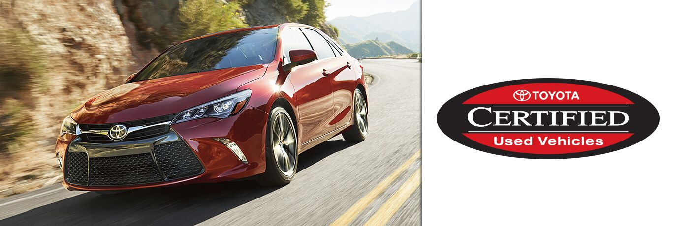 """Red Toyota Camry drives up a highway. Logo on the right says, """"Toyota CERTIFIED Used Vehicles."""""""
