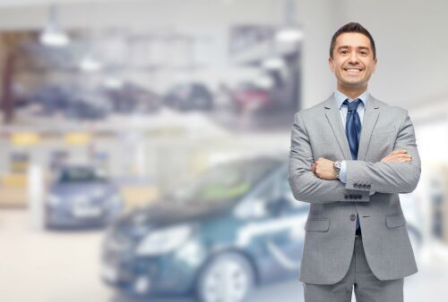 A well-dressed salesman crosses his arms and smiles in a showroom.