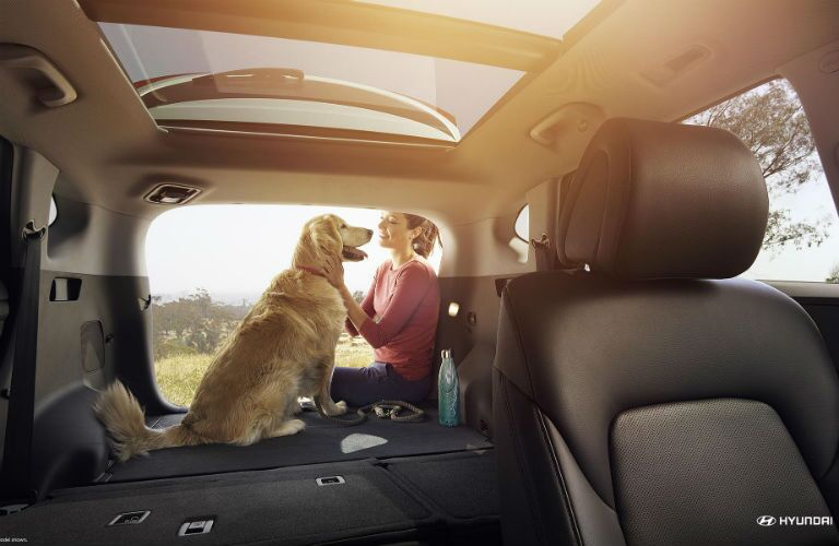 rear cargo area of a 2018 Hyundai Tucson with rear seats down and a woman with her dog