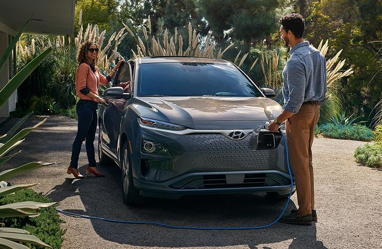 a couple washing a silver 2019 Hyundai Kona