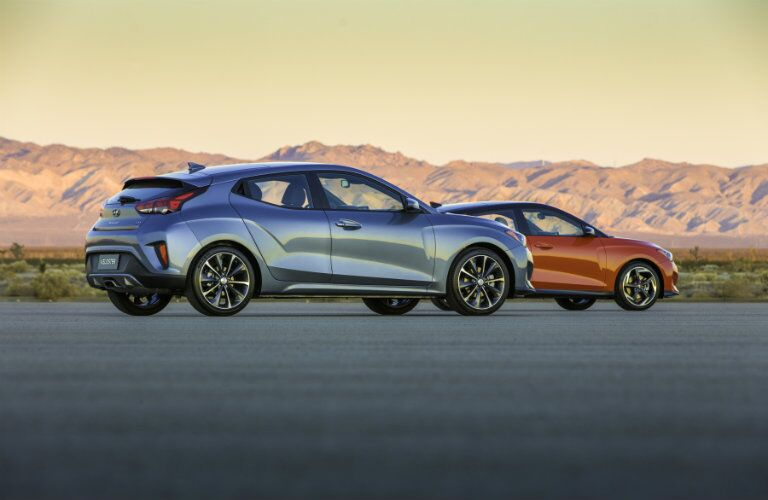 side view of two 2019 Hyundai Veloster models, one silver and one orange