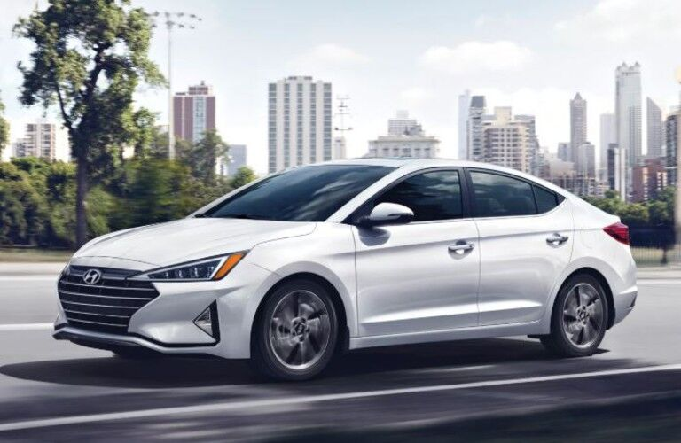 White 2020 Hyundai Elantra drives down a highway with a city skyline in the background.