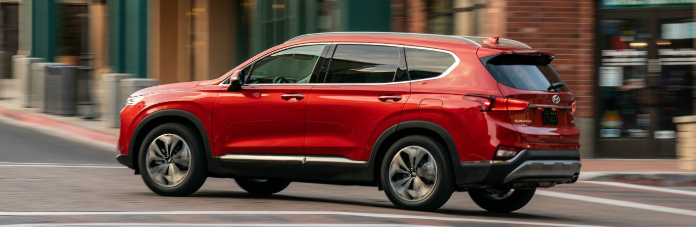 Red 2020 Hyundai Santa Fe rolls around a deserted city corner.