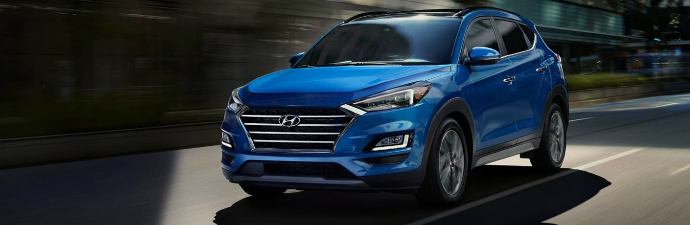 Blue 2020 Hyundai Tucson drives up a city street.