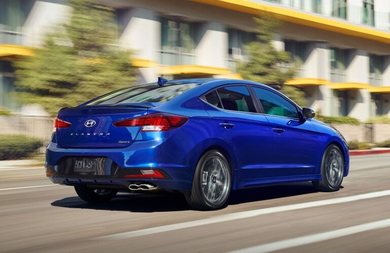 Blue 2020 Hyundai Elantra drives through a sun-drenched city.