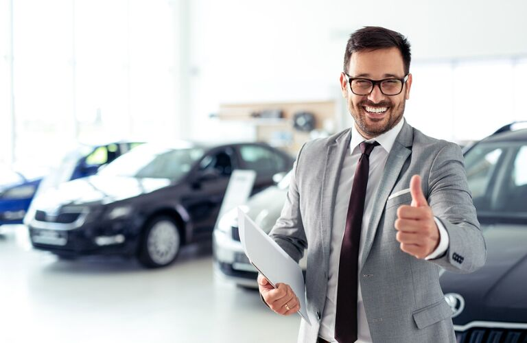 A grinning salesman gives the thumbs up in a car showroom.