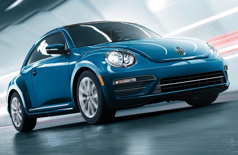 Blue Volkswagen Beetle drives through a tunnel