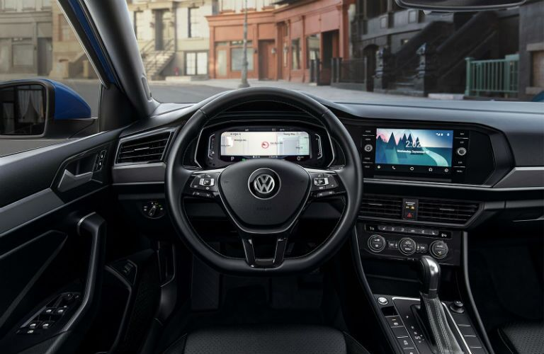 Interior front cabin of a 2019 Volkswagen Jetta as it drives through a European city.