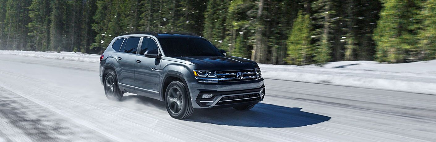2020 Volkswagen Atlas drives up a snowy road beside some pines