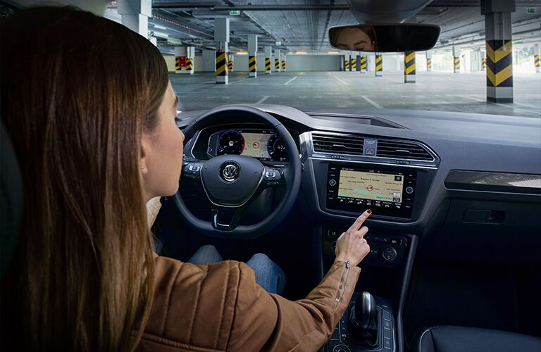 Woman extends finger to infotainment screen inside 2020 VW Tiguan.