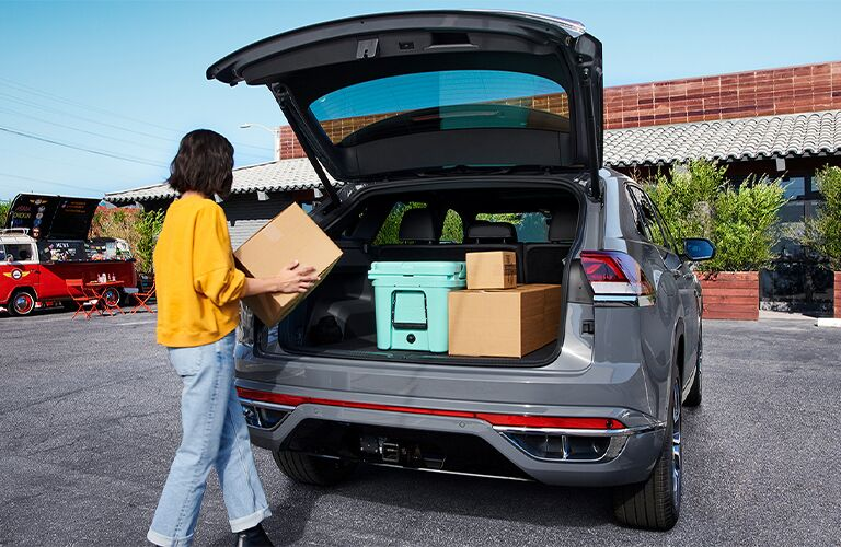 Woman moves to put a box inside the cargo area of a 2021 Volkswagen Atlas Cross Sport