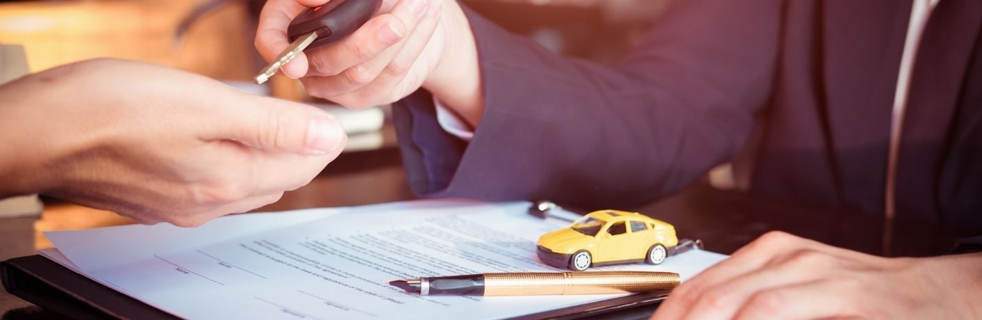 Man hands key to woman over warranty with a tiny car model sitting on it