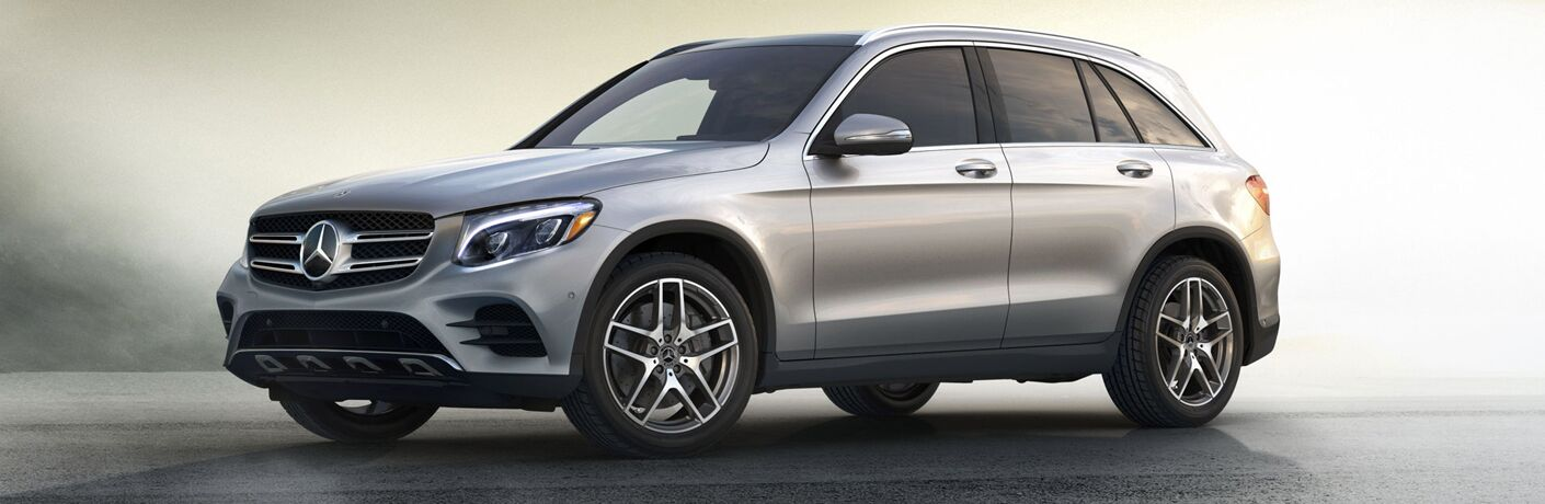 Silver 2018 Mercedes-Benz GLC SUV against an abstract background.