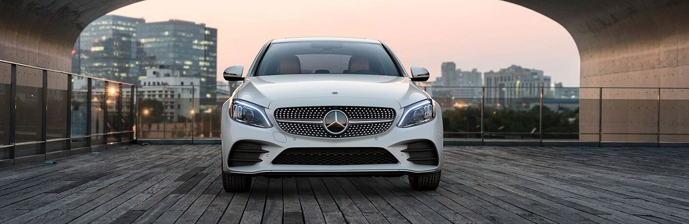 White 2020 Mercedes-Benz C-Class sits on a deck under a big arch.