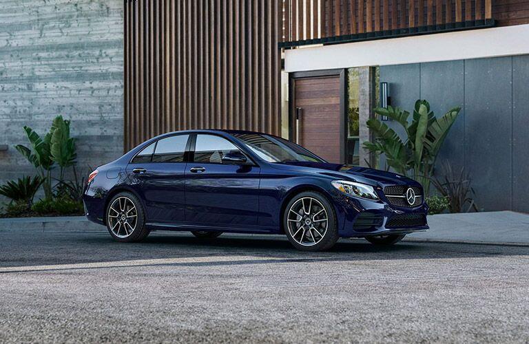 Blue 2020 Mercedes-Benz C-Class sedan parked beside an unmarked building.