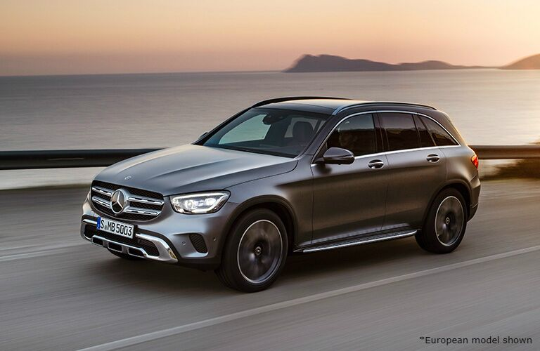 Silver 2020 Mercedes-Benz GLC drives along a highway beside the ocean as the sun sets.