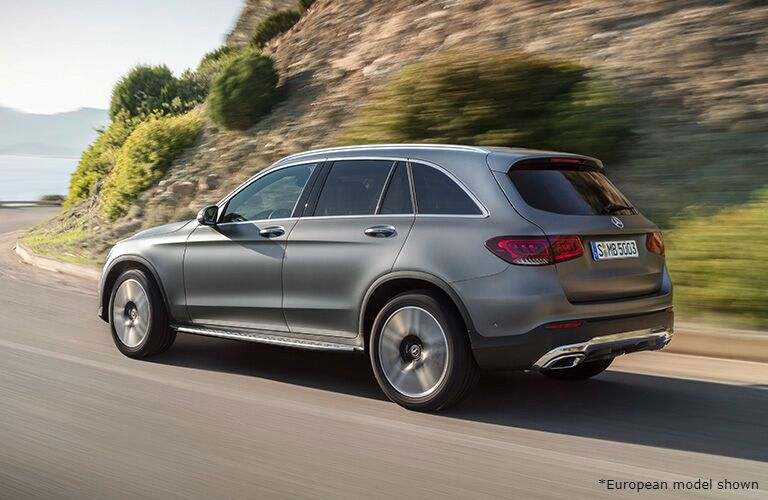 Silver 2020 Mercedes-Benz GLC drives around a corner on a tropical highway.