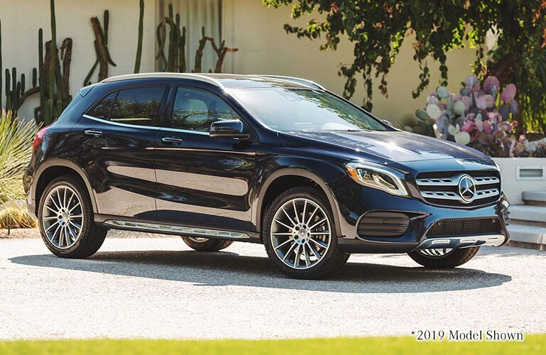 Blue 2020 Mercedes-Benz GLA SUV parked by a sunny garden.
