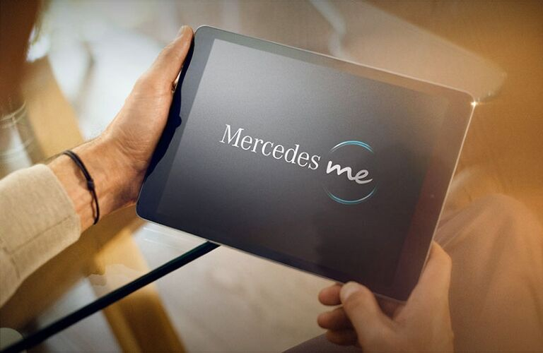 Person holds a tablet with Mercedes me on the screen