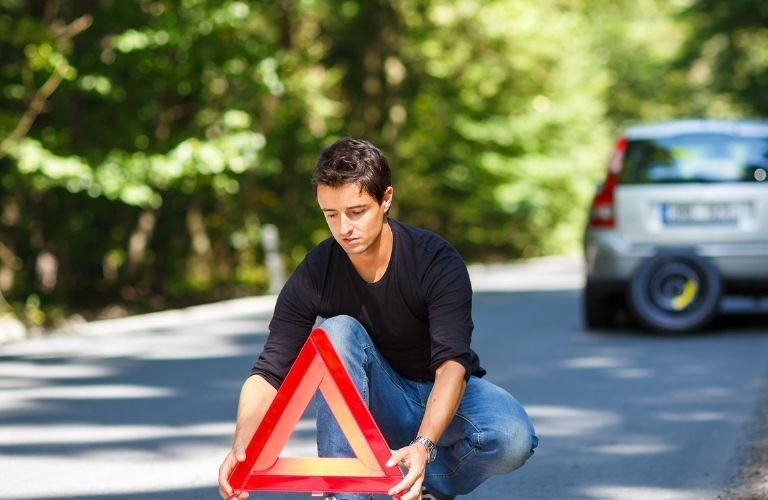 A man setting up a roadblock sign