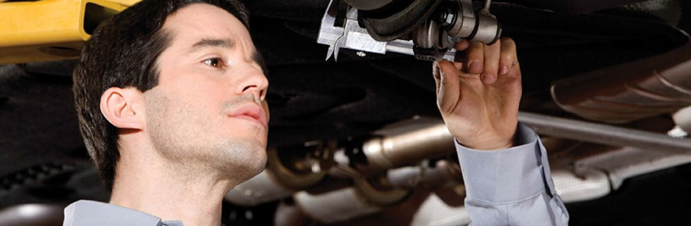 Man looks closely at a part on a Mercedes-Benz vehicle.