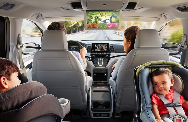 Parents in the front of the car while two children ride in the back