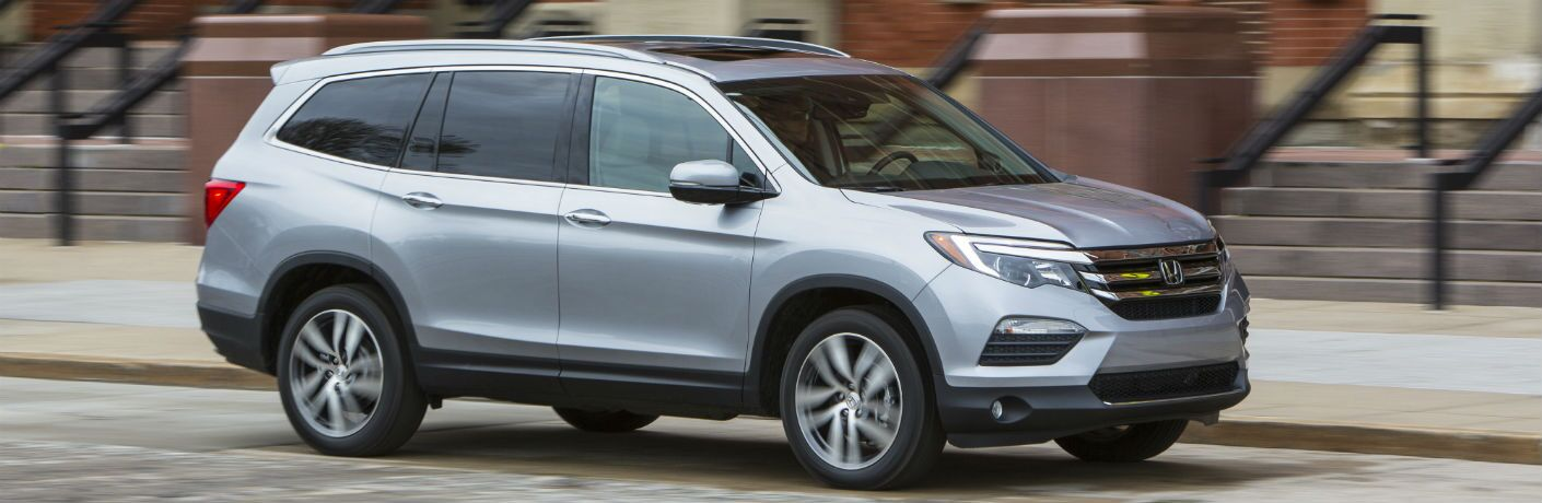 side view of silver 2018 Honda Pilot driving on urban street
