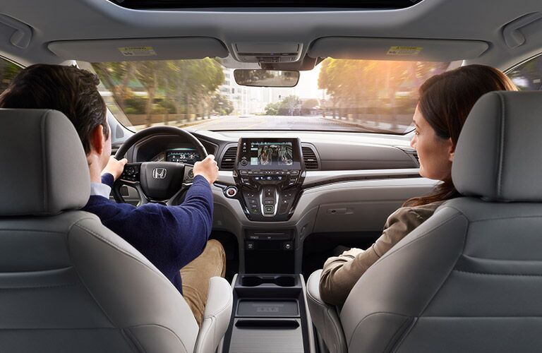 Dad driving the Honda Odyssey while the mom talks to him