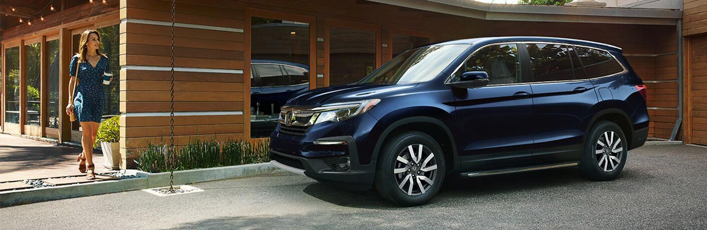 A woman walks towards a 2019 Honda Pilot parked in front of a building