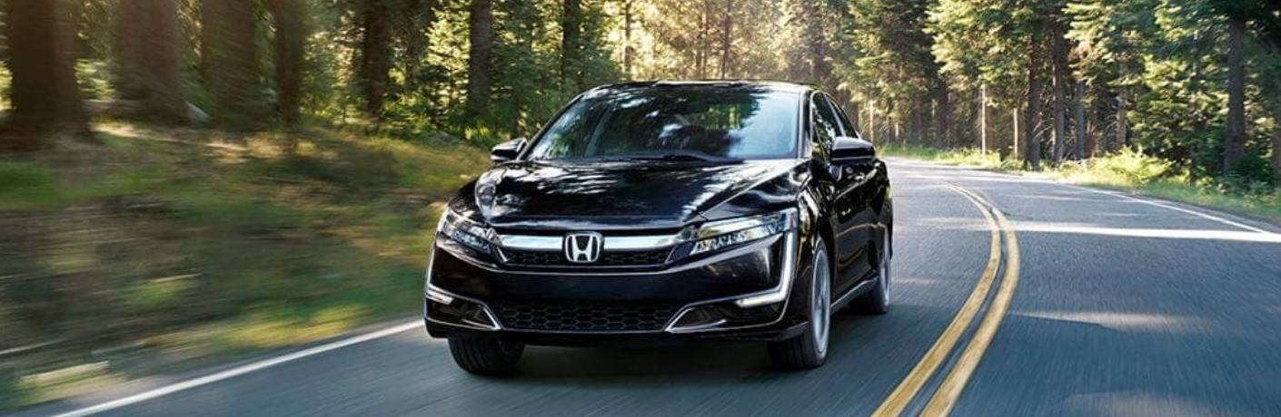 2019 Honda Clarity Plug-In Hybrid driving down a forested road