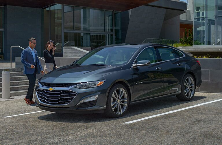 2019 Chevy Malibu in parking lot by businesspeople