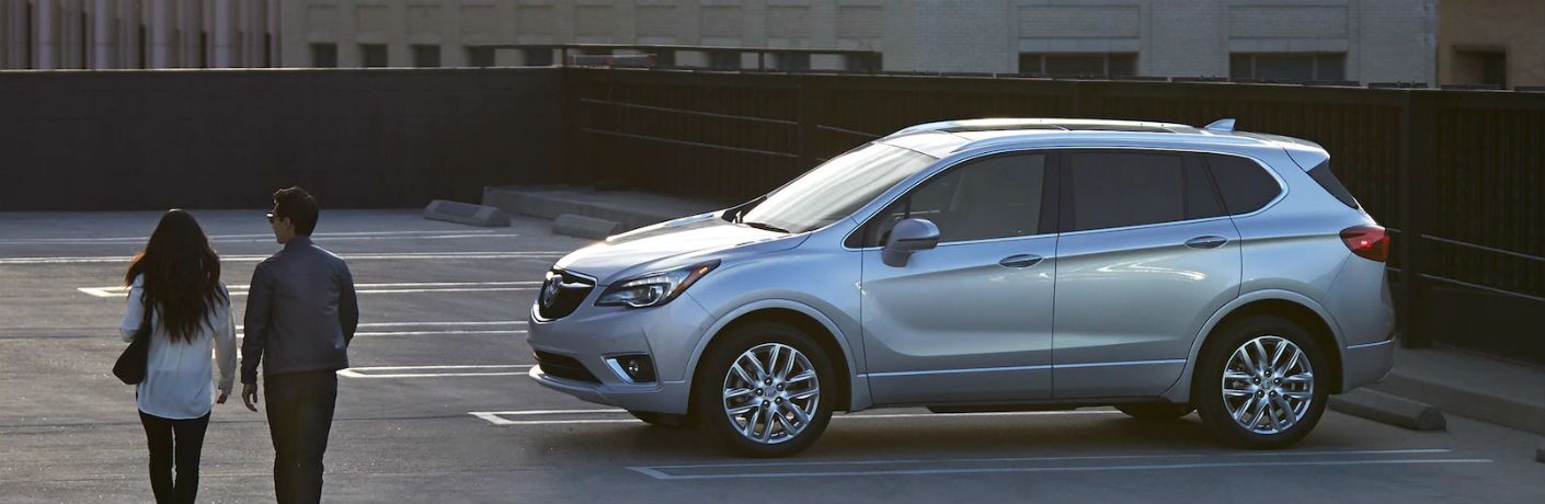 2019 Buick Envision exterior drivers side profile with couple walking to left of photo