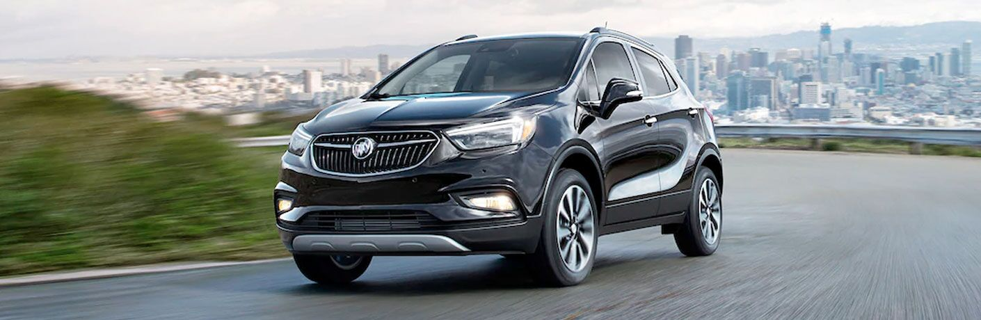 Black 2020 Buick Encore driving on a road near a city