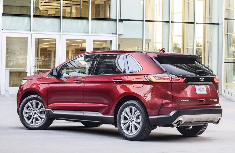 2020 Ford Edge exterior back fascia and driver side in front of building with glass windows