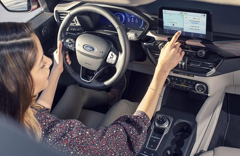Woman using touchscreen navigation system in 2020 Ford Escape