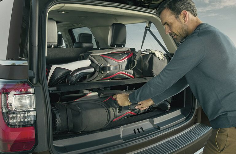 Man packing belongings into cargo area of 2020 Ford Expedition